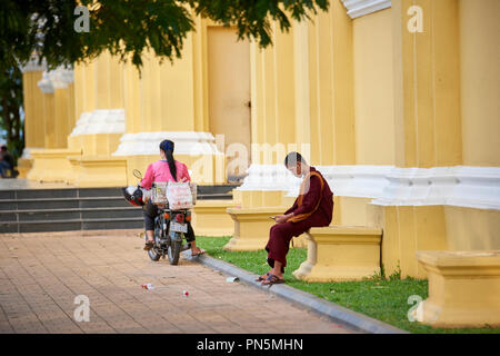 A young Buddhist monk sitting in a park looking at his mobile phone in Phnom Penh, Cambodia. - Stock Image