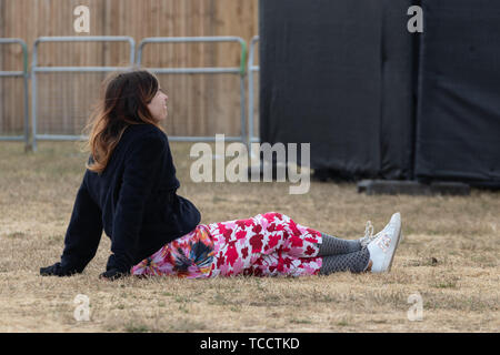 A woman sat on the grass at an open air festival enjoying the show - Stock Image