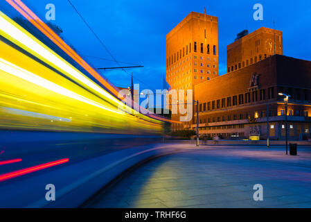 Oslo city centre, view at night of a city tram speeding towards the Town Hall building (Radhus) in the central harbour district of Oslo, Norway. - Stock Image