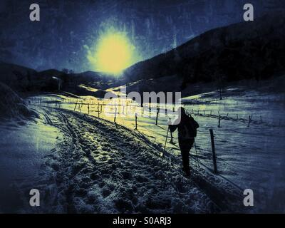 Nordic / cross-country Skier in a snow covered valley skiing towards the sun. - Stock Image