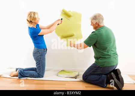 Middle aged couple beginning to paint wall green over drop cloth - Stock Image