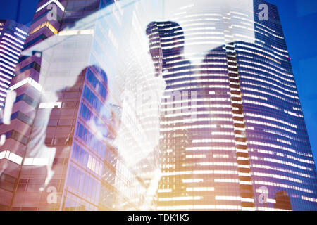 Businessmen that work together in office at night. Concept of teamwork and partnership. double exposure - Stock Image