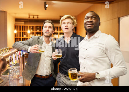 Three multicultural friends watch a football match in a pub together - Stock Image
