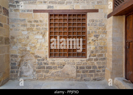 Mamluk era wooden closed window with wooden ornate grid over stone bricks wall, Tekkeyet Al Bustami, Dar El Labbana district, Cairo, Egypt - Stock Image