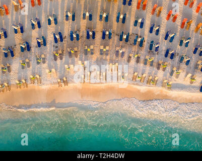 Aerial view of a beach in Greece with sunchairs and umbrellas in morning light at sunrise - Stock Image