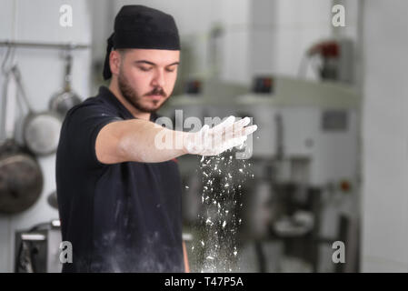 Baker, pouring flour over the bread dough at the bakery kitchen . - Stock Image