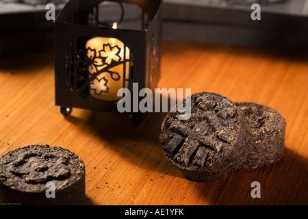 Tea rolls on a table adorned with distinct designs near a lit candle. - Stock Image