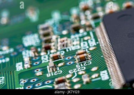 Surface mount technology (SMT) components on a green printed circuitboard. Wiring inside computer. - Stock Image