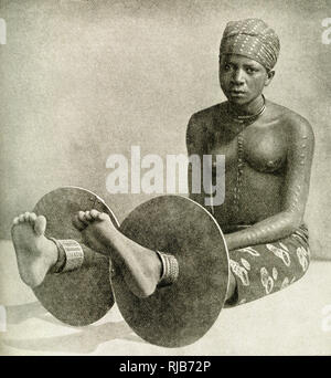 Young Ibo (Igbo) woman wearing metal ankle plates (anklets), Nigeria, West Africa. Apparently a fashion rather than punishment, it is claimed that many of the metal plates were made in Birmingham. - Stock Image