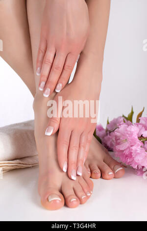 Girl legs with bare feet and hands with french manicure and pedicure on white towel in spa salon and decorative pink flower in background - Stock Image