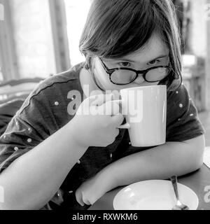 Young girl with Downs Syndrome having afternoon tea at White Mill Mariana, Northamptonshire. - Stock Image