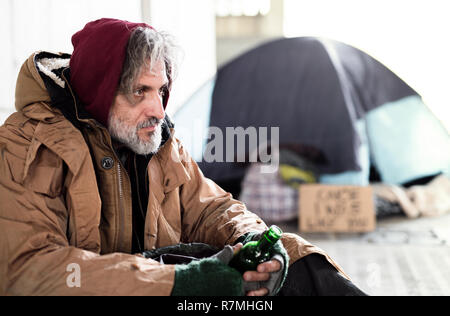 A homeless beggar man sitting outdoors in city asking for money donation, holding a bottle of alcohol. Copy space. - Stock Image