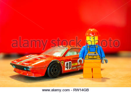 Poznan, Poland - February 15, 2019: Lego construction worker figure standing next to his parked red Ferrari GTO racing car. - Stock Image