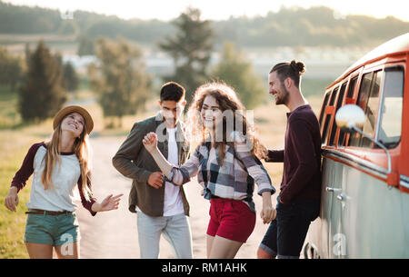 A group of young friends on a roadtrip through countryside, dancing. - Stock Image