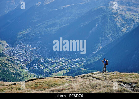 Hiker on grassy cliff overlooking valley, Mont Cervin, Matterhorn, Valais, Switzerland - Stock Image