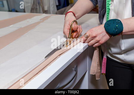 Female hands are cutting the fabric with tailors' scissors on the pattern of paper, on a white table - Stock Image