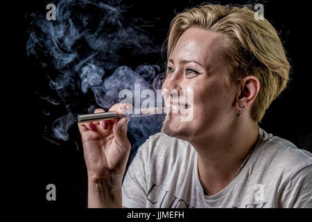 Young adult female exhaling smoke clouds from electronic cigarette and smiling - Stock Image