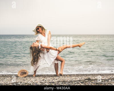 Adult woman wearing a white dress and her daughter wlaking on the  beach. - Stock Image