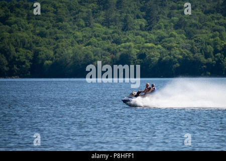 A fast jet propelled personal watercraft skimming over the water on Lake Pleasant, NY in the Adirondack Mountains. - Stock Image