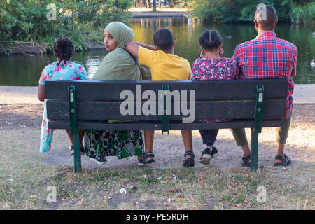 A muslim family enjoy the evening sunshine on a park bench in a London park - Stock Image