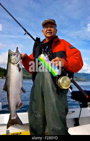 Asian male angler holding sport caught chinook salmon Chatham Point Campbell River BC Canada - Stock Image