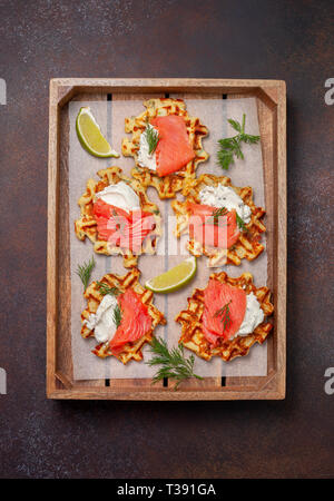 potato waffles with salmon, cream cheese on a wooden tray. view from above - Stock Image
