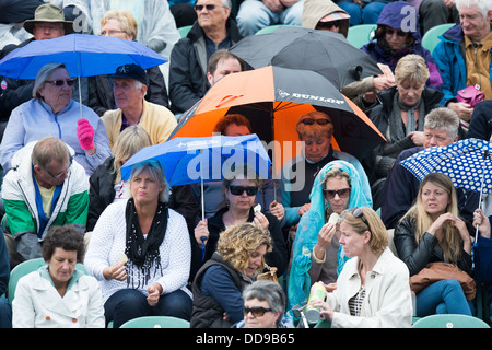 Crowd enjoys a picnic lunch under umbrellas and ponchos for cover during a break in a tennis match in Eastbourne, - Stock Image