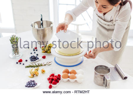 creative confectioner smoothing the top of the cake. close up cropped photo - Stock Image