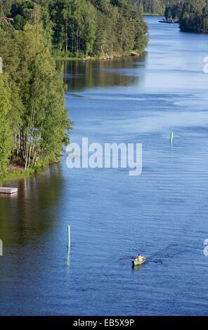 Man rowing a rowboat at Leppävirta river , Finland - Stock Image