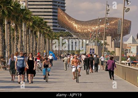 Spain Barcelona beach Platja de la Barceloneta promenade people background ffish sculture by Frank Gehry  - Stock Image