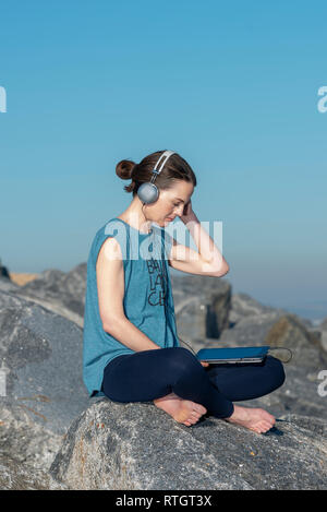 woman sitting on rocks by the sea listening to music on her tablet with headphones - Stock Image
