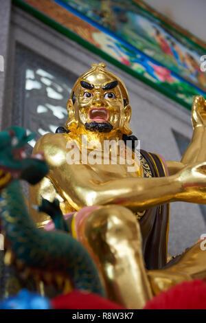 Detail of Gilt Lohan Arhat taming a dragon, inside Kuang Im Chapel, near River Kwai, Kanchanaburi, Thailand. - Stock Image