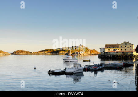 Fishing boats are moored at a jetty in Henningsvaer on Lofoten in northern Norway. - Stock Image