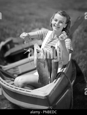 1940s SMILING YOUNG WOMAN SITTING IN ROW BOAT LOOKING AT CAMERA HOLDING UP NICE CATCH OF FISH - a2809 DEB001 HARS CELEBRATION FEMALES PROUD RURAL HOME LIFE NATURE COPY SPACE CATCH HALF-LENGTH LADIES PERSONS ATHLETIC EXPRESSIONS B&W EYE CONTACT CATCHING NICE SUCCESS HAPPINESS CHEERFUL HIGH ANGLE ADVENTURE LEISURE STRENGTH EXCITEMENT RECREATION PRIDE IN OF UP SMILES JOYFUL STYLISH DEB001 SHOWING OFF RELAXATION WILDLIFE YOUNG ADULT WOMAN BLACK AND WHITE CAUCASIAN ETHNICITY OLD FASHIONED - Stock Image