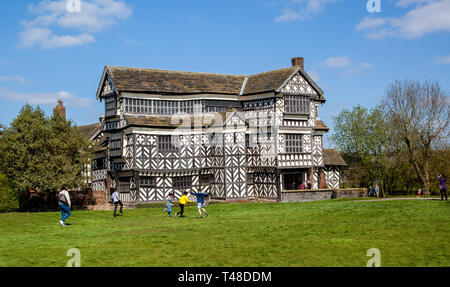 Family at Little Moreton Hall, black and white half timbered Tudor manor house near Congleton in Cheshire, owned by the national trust - Stock Image