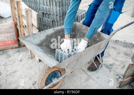 Builder loading paving tiles into the pushcart standing on the construction site, close-up view with no face - Stock Image