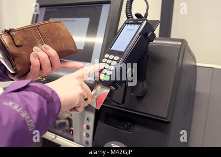 A female shopper using a chip and pin card reader machine to pay for goods using a credit card. She is entering - Stock Image