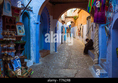 Chefchaouen, Morocco : A man sits under an arch in the blue-washed alleyways of the medina old town. - Stock Image