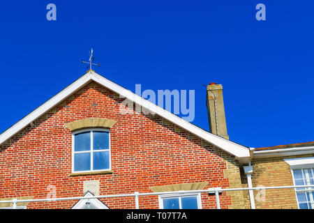 Close crop of a English red brick house against a cloudless blue sky - Stock Image