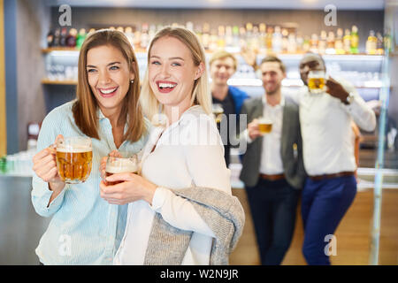 Two friends celebrate with beer in a pub or pub - Stock Image