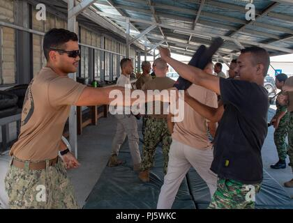 Master-at-Arms 2nd Class Bernard Servillas, from St. Joseph, Michigan, assigned to Coastal Riverine Group (CRG) 1 Det. Guam, and a member of the Timor-Leste Defense Force practice baton strikes during CARAT Timor-Leste 2018 at Hera Naval Base, Aug. 28, 2018. CARAT Timor-Leste 2018 is designed to address shared maritime security concerns, build relationships and enhance interoperability among participating forces. (U.S. Navy photo by Mass Communication Specialist 3rd Class Danny Ray Nuñez Jr./Released) - Stock Image