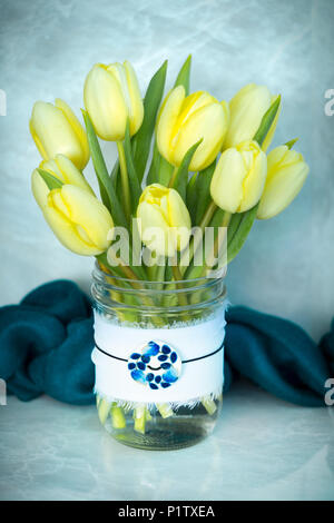 Cut tulips in a decorative glass jar with a pendant - Stock Image