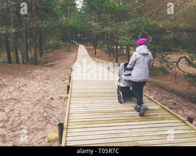 woman with stroller walking on wooden pedestrian path in forest - Stock Image