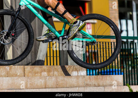Cyclist on a mountain bike doing bike tricks on stairs in the city - Stock Image