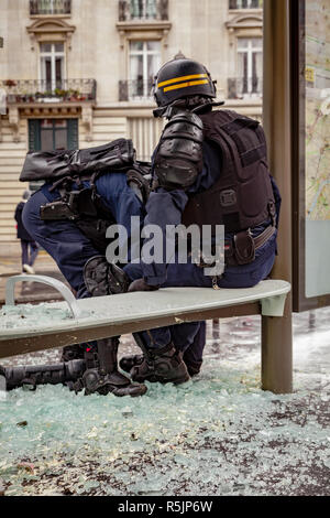 Paris, France. 1st December, 2018.  Policemen in front of a destroyed bus stop during the Yellow Vests protest against Macron politic. Credit: Guillaume Louyot/Alamy Live News - Stock Image