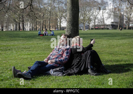 St James's Park, London. 22nd Feb 2019. UK Weather: Springtime in London. Constantine and Inna, from Latvia, enjoing the sunshine in Green Park, London, UK. Credit: amanda rose/Alamy Live News - Stock Image