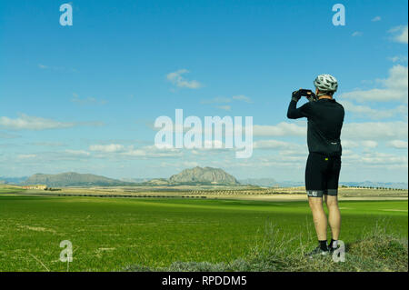 Cyclist pauses to photograph landscape on a beautiful February winter day in Valle de Ricote, Murcia, Spain. - Stock Image
