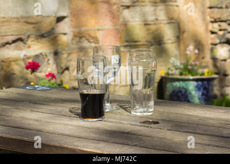 Three empty or half empty beer and wine glasses on a outside wooden pub table in a beer garden. The glasses are branded Guinness, Stowells and Fosters - Stock Image