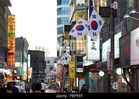 Commercial street in Seoul, South Korea, with row of South Korean flags. - Stock Image