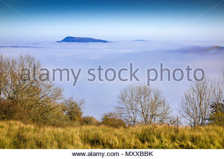 Fog caused by temperature inversion fill the River Usk valley. The peak of Great Skirrid (Big Skirrid) is in the distance; Monmouthshire, Wales, UK. - Stock Image